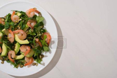 Photo pour Vue de dessus de la salade verte fraîche avec des graines de citrouille, crevettes et avocat sur fond blanc - image libre de droit