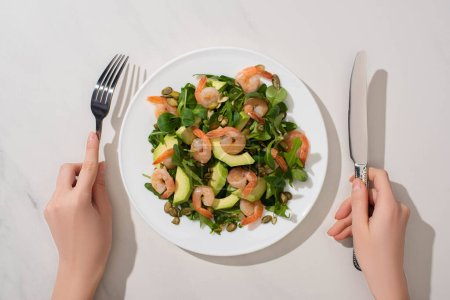 partial view of woman eating fresh green salad with pumpkin seeds, shrimps and avocado on white background