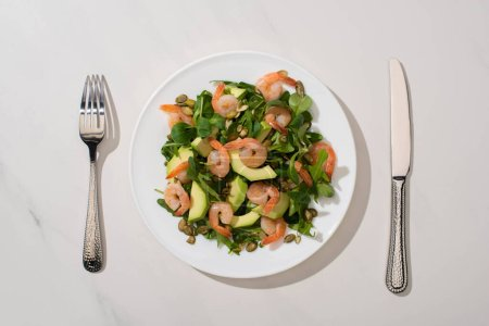 Photo for Top view of fresh green salad with pumpkin seeds, shrimps and avocado on plate near cutlery on white background - Royalty Free Image