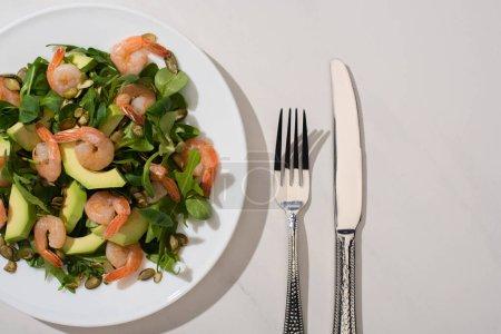 Draufsicht auf frischen grünen Salat mit Kürbiskernen, Garnelen und Avocado auf Teller neben Besteck auf weißem Hintergrund