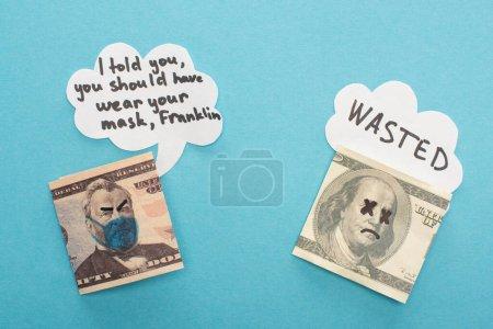 Photo pour Vue du haut des billets en dollars avec masque médical dessiné et bulles d'expression sur fond bleu - image libre de droit