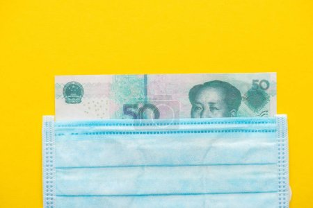 top view of banknote and medical mask on yellow background