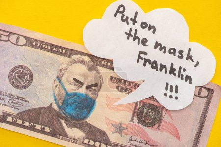 banknote with drawn medical mask and angry face expression near speech bubble on yellow background