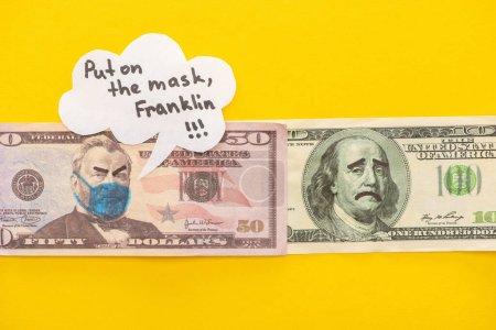 Photo pour Vue du haut des billets avec masque médical dessiné et expressions faciales près de la bulle d'expression sur fond jaune - image libre de droit