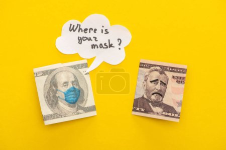 Photo for Top view of banknotes with drawn medical mask and face expressions near speech bubble on yellow background - Royalty Free Image