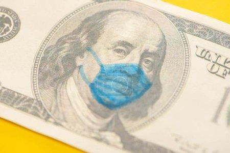 Photo pour Vue rapprochée du billet en dollar avec masque médical dessiné sur fond jaune - image libre de droit