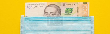 top view of Ukrainian banknote and medical mask on yellow background, panoramic shot