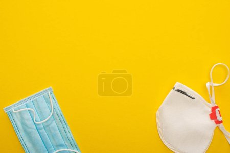 top view of medical and safety masks on yellow background