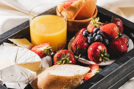 Photo for Close up view of french breakfast with grapefruit, Camembert, orange juice, berries and baguette on wooden tray - Royalty Free Image