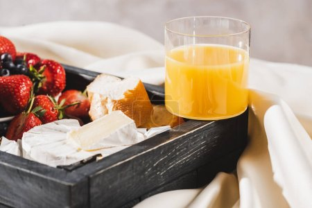 Photo for Close up view of french breakfast with Camembert, orange juice, berries and baguette on wooden tray on textured white cloth - Royalty Free Image