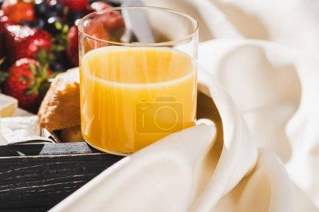 Photo pour Vue rapprochée du petit déjeuner français avec jus d'orange, baies sur plateau en bois sur toile blanche texturée - image libre de droit