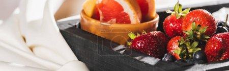 Photo pour Vue rapprochée du petit déjeuner français avec pamplemousse, baies sur plateau en bois sur toile blanche texturée, vue panoramique - image libre de droit