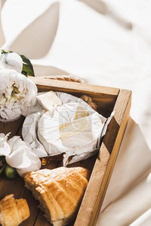 close up view of french breakfast with croissant, Camembert on wooden tray on textured white cloth with peony