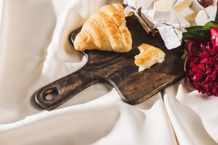 top view of french breakfast with croissant, Camembert, peony on wooden cutting board on white tablecloth