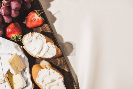 Photo for Top view of of french breakfast with baguette, Camembert, strawberries and grape on wooden cutting board on white tablecloth - Royalty Free Image