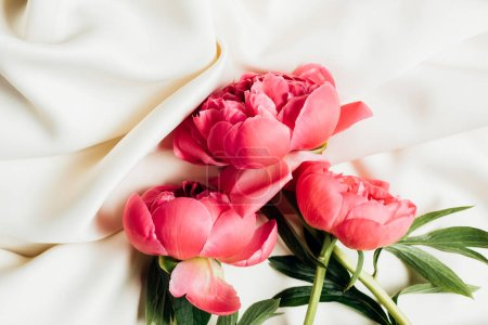 Photo for Top view of bouquet of pink peonies on white cloth - Royalty Free Image