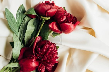 Photo for Top view of bouquet of red peonies on white cloth - Royalty Free Image