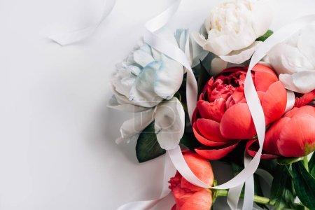 Photo pour Vue de dessus des pivoines roses et blanches avec ruban sur fond blanc - image libre de droit