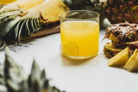 Photo pour Foyer sélectif de jus d'ananas frais près de fruits délicieux coupés sur fond blanc - image libre de droit
