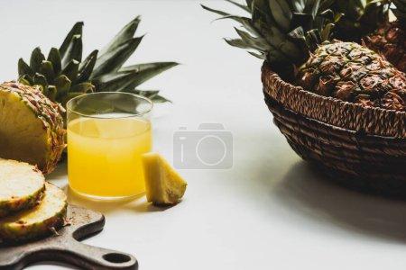 Photo pour Jus d'ananas frais près de fruits délicieux coupés sur planche à découper en bois et dans un bol sur fond blanc - image libre de droit