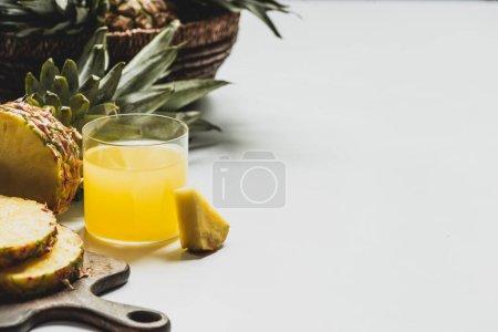 Photo pour Jus d'ananas frais près de fruits délicieux coupés sur planche à découper en bois sur fond blanc - image libre de droit