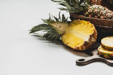 Photo for Fresh cut delicious pineapple on wooden cutting board and in basket on white background - Royalty Free Image