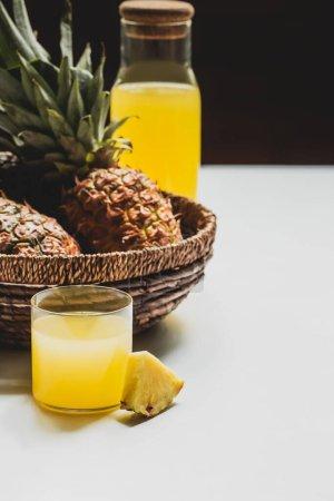 Photo pour Foyer sélectif de jus d'ananas frais en verre et bouteille près de délicieux fruits dans le panier sur fond blanc isolé sur noir - image libre de droit