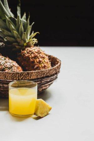 Foto de Zumo de piña fresca cerca de deliciosa fruta en cesta sobre fondo blanco aislado en negro - Imagen libre de derechos