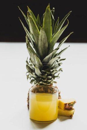 frischer Ananassaft im Glas in der Nähe geschnitten köstliche Früchte auf weißer Oberfläche isoliert auf schwarzer