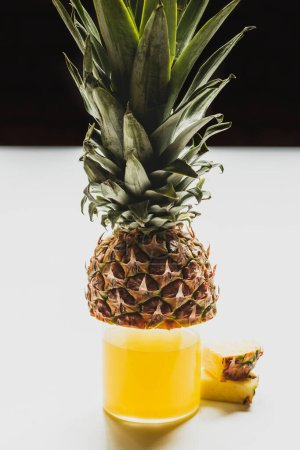 Photo for Fresh pineapple juice in glass near cut delicious fruit on white surface isolated on black - Royalty Free Image