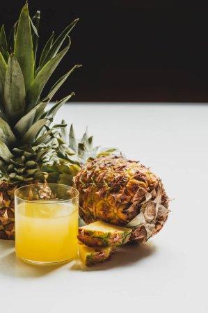 Photo pour Jus d'ananas frais près de fruits délicieux coupés sur surface blanche isolé sur noir - image libre de droit