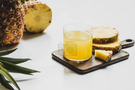 zumo de piña fresca en vidrio cerca de corte deliciosa fruta en tabla de cortar de madera sobre fondo blanco