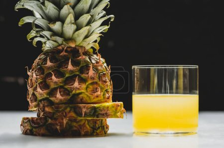 Photo for Fresh pineapple juice and cut delicious fruit on white surface on black background - Royalty Free Image