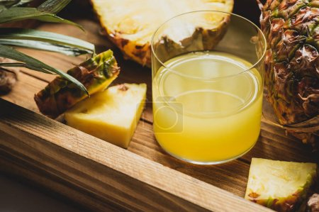 close up view of fresh pineapple juice and cut delicious fruit on wooden tray
