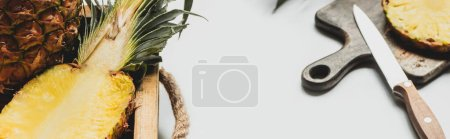 Photo for Selective focus of fresh cut pineapple on wooden tray and cutting board with knife on white background, panoramic orientation - Royalty Free Image