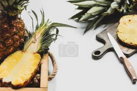 Photo for Selective focus of fresh cut pineapple on wooden tray and cutting board with knife on white background - Royalty Free Image