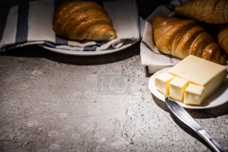 Photo for Selective focus of fresh baked croissants on towel near butter and knife on concrete grey surface in dark - Royalty Free Image