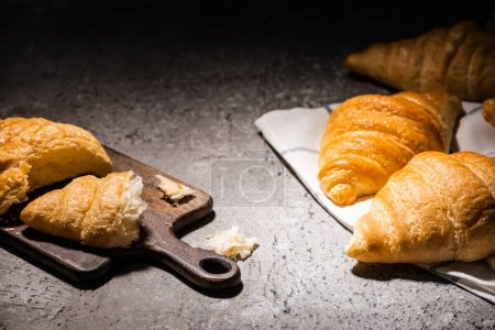 Photo for Fresh baked croissants on towel near cutting board on concrete grey surface in dark - Royalty Free Image