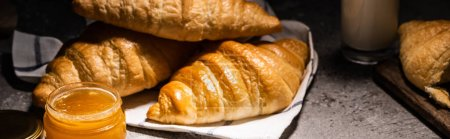 Photo for Fresh baked croissants on towel near jam on concrete grey surface in dark, panoramic shot - Royalty Free Image