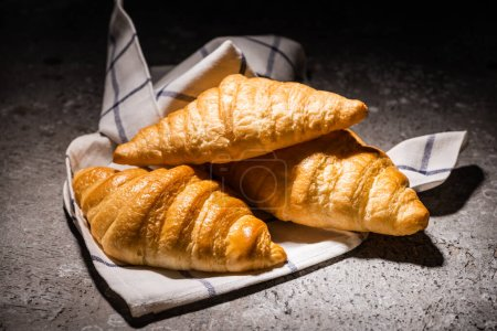 Photo for Fresh baked croissants on towel on concrete grey surface in dark - Royalty Free Image