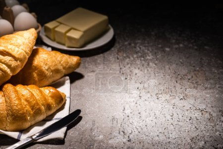 Photo for Selective focus of fresh baked croissants with knife on towel near butter and eggs on concrete grey surface in dark - Royalty Free Image