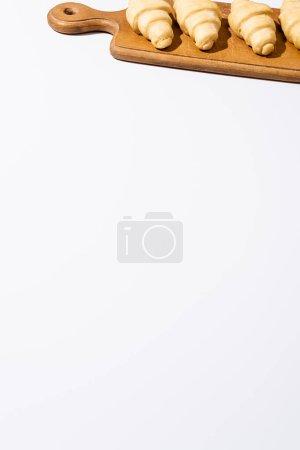 Photo pour Croissants crus sur planche à découper en bois isolé sur fond blanc - image libre de droit