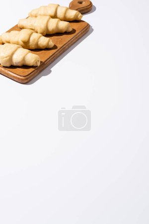 Photo for Raw croissants on wooden cutting board on white background - Royalty Free Image