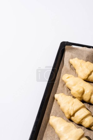 Photo for Raw croissants on baking tray isolated on white background - Royalty Free Image
