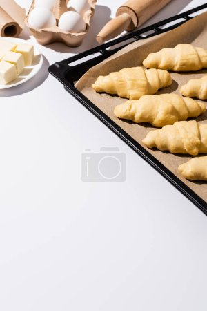 Photo for Selective focus of raw croissants on baking tray near rolling pin, parchment paper, butter, eggs on white background - Royalty Free Image