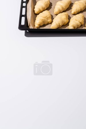 Photo for Raw croissants on baking tray on white background - Royalty Free Image
