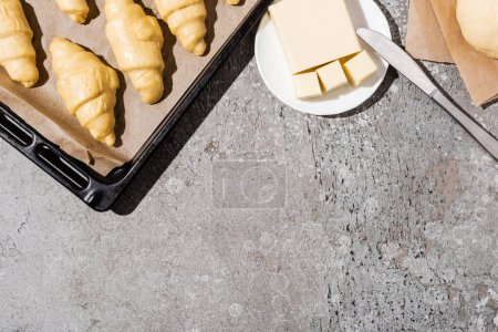 Photo for Top view of uncooked croissants on baking tray near dough and butter on concrete grey surface - Royalty Free Image