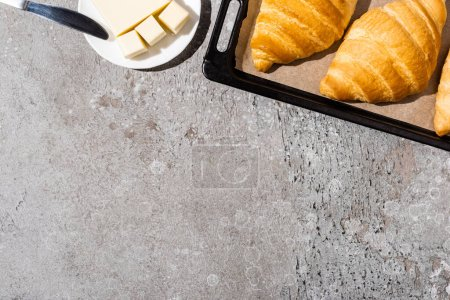 Photo for Top view of baked delicious croissants on baking tray near butter on concrete grey surface - Royalty Free Image