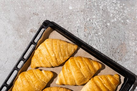 Photo for Top view of baked delicious croissants on baking tray on concrete grey surface - Royalty Free Image