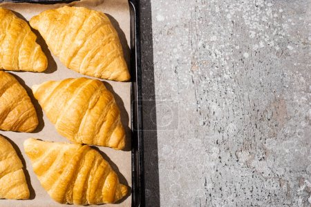 top view of baked delicious croissants on baking tray on concrete grey surface